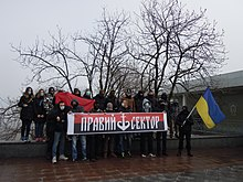 twenty masked activists posing with a Ukrainian flag and a Right Sector banner showing trident as ship anchor at a Euromaidan event in Odessa