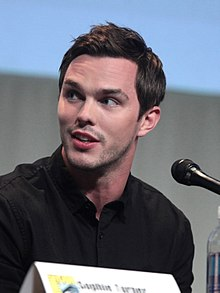 A young, Caucasian man with short, dark hair and facial stubble wearing a black shirt speaks into a microphone against a grey and blue background.