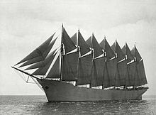 A seven-masted schooner outfit with sails sits high in the water