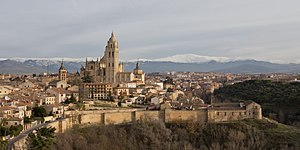 Segovia - View of the façade of the Segovia Cathedral, the ancient City Walls (8th century), and the Guadarrama mountains.