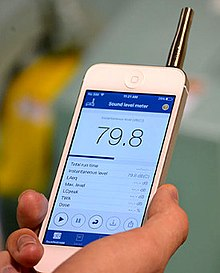 An image of a person holding a smartphone displaying the NIOSH sound level meter application (app)