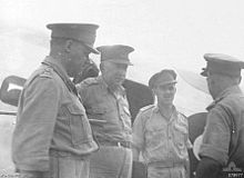 Four men in uniform with peaked caps talking to each other.