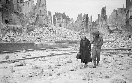 A British soldier escorts an elderly lady in Caen, July 1944 The Allied Campaign in North-west Europe, 6 June 1944 - 7 May 1945 B6794.jpg