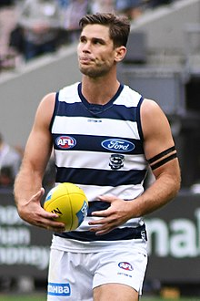 A brown-haired man in a sleeveless white and navy-hooped guernsey holding a yellow football