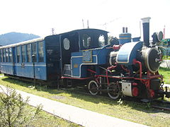 Blue locomotive and two passenger carriages