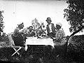Tre män, en kvinna och en flicka kring ett dukat middagsbord utomhus. Två av männen höjer sina nubbeglas och skålar - Nordiska Museet - NMA.0057481.jpg