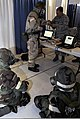 U.S. Airmen taking part in a financial management competition don mission-oriented protective posture gear and stay low during a chemical warfare scenario July 25, 2011, during Air Mobility Rodeo 2011 at Joint 110725-F-FC636-010.jpg