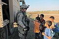 U.S. Army Spc. Harrell, left, assigned to Bravo Company, 2nd Battalion, 8th Cavalry Regiment, 1st Brigade, 1st Cavalry Division demonstrates the strength of body armor to Iraqi children outside of a police 111030-A-PQ424-002.jpg