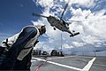 U.S. Navy Chief Boatswain's Mate Jabari Turner braces himself as an SH-60B Seahawk helicopter assigned to Helicopter Combat Support Squadron (HSC) 25 delivers supplies to the guided missile destroyer USS 130813-N-TX154-047.jpg