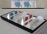Unsichtbarkeits-Paradoxon mit Zylinder-Linsen-Hälften: das Bild oben sieht ein Betrachter, der durch die halbe Zylinderlinse unten rechts auf die roten Tiere blickt; diese sind jedoch nicht zu sehen, da die Strahlung der blauen Tiere durch den unter den roten Tieren auf dem Spiegel liegenden Linienfokus zum Betrachter gelangt, Die beiden Zylinderlinsenhälften sind hierzu konfokal aufgestellt.
