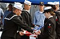 US Navy 040315-N-4929B-038 Sailors aboard the guided missile destroyer USS Pinckney (DDG 91) fold an American flag during a memorial service honoring three Pinckney Sailors who were killed in a bus accident on March 12.jpg
