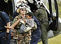 US Navy 050106-N-4166B-282 Lt. Shawn Harris, assigned to the guided missile destroyer USS Shoup (DDG 86), carries an injured boy from an MH-60S Knighthawk helicopter to a triage site.jpg