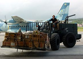 US Navy 050123-N-8801B-167 U.S. Air Force Staff Sgt. Austin Bretwell, assigned to the 615th Air Mobility Operations Group, drives a five ton forklift as he transports food, clothing and relief supplies from a warehouse to await.jpg
