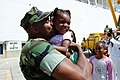 US Navy 050608-N-6504N-007 Storekeeper 2nd Class Erik Underwood kisses his daughter after getting off the Military Sealift Command (MSC) hospital ship USNS Mercy (T-AH 19).jpg