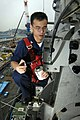 US Navy 050831-N-9389D-024 Information Systems Technician 2nd Class Luan Nguyen of Salt Lake City, applies dry glue to the bolts and nuts that secure a whip antenna aboard the conventionally powered aircraft carrier USS Kitty H.jpg