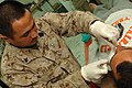 US Navy 061220-N-5758H-086 Hospital Corpsman 3rd Class Aloen Delapena, assigned to the 1st Medical Battalion, Camp Pendleton, applies clean bandages to a wound on the face of an Iraqi citizen.jpg