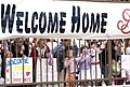 US Navy 070420-N-9712C-004 Families and friends of Sailors embarked on board USS Ronald Reagan (CVN 76) gather on the pier at Naval Air Station North Island to greet the Sailors as the ship returns home from deployment.jpg