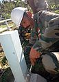 US Navy 070820-N-9421C-011 A Soldier from the Indian army tightens a lug nut on a foundation for a hut being built during an engineering civic action program at the Sasamungga Hospital, in support of the Pacific Partnership mis.jpg