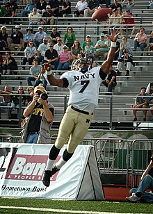 An American football player in a gold and white uniform strains to catch a football out of reach.