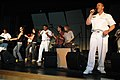 US Navy 090527-N-7975R-006 Musician 1st Class Ira Ostrowski sings lead vocals with the Naval Academy Band, the Electric Brigade, as Chief Musician Frank Dominguez dances with students during a performance at Irondequoit High.jpg