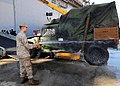 US Navy 091024-N-4680O-016 A Marine assigned to the 22nd Marine Expeditionary Unit washed the dirt from a Humvee as it is loaded aboard the multipurpose amphibious assault ship USS Bataan.jpg