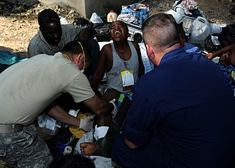 Sympathy - Medical personnel aid a suffering woman after the 2010 Haiti earthquake.