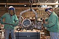US Navy 111021-N-ZZ999-001 Shipbuilders Jason West, left, and Kevin Forrest pour molten pewter into a mold for production of the Quicken Loans Carr.jpg