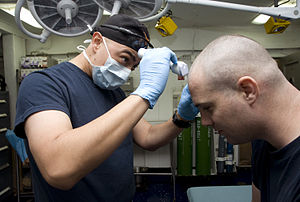 US Navy 120120-N-JN664-010 Hospital Corpsman 1st Class Albert Aguilar shaves the head of Mass Communication Specialist 2nd Class Christopher Dollar.jpg