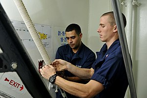 US Navy 120121-N-ZI635-051 Seaman Brenson Sanchez and Boatswain's Mate 2nd Class Kenneth E. Haley tie a series of cox combing knots on a handrail l.jpg