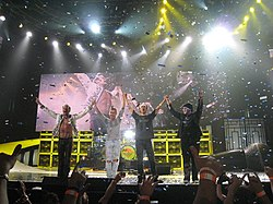 Van Halen standing onstage and waving to the audience
