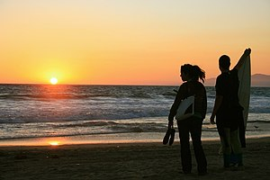 California Sound - A young couple watching the sunset on a Los Angeles beach with surfboard in hand
