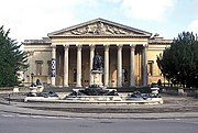 A Palladian style nineteenth century stone building with a large colonnaded porch. In front a large metal statue on a pedestal and fountains with decorations.