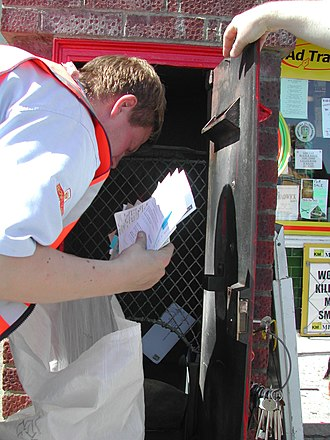 Wall box - The tablet holder box and the Chubb lock are clearly visible as a postman clears mail from an 'A' size wall box in Deal, Kent