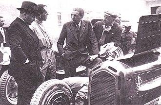 "Eduardo Weber - Edoardo Weber at far left (around 1933). The others are (from left): Giulio Ramponi, Carlo Felice Trossi and Enzo Ferrari of the Scuderia Ferrari team. The car is an Alfa Romeo 8C ""Monza""."