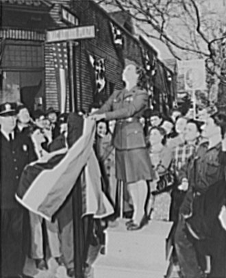 Westinghouse Lamp Plant - A woman is shown unveiling the new street sign of MacArthur Avenue and MacArthur Plaza.