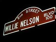"A sign of a street that reads ""2nd street, Willie Nelson BLVD 100"". It is night time and the sign is lighted, the borders and letters are white and the inside is red."