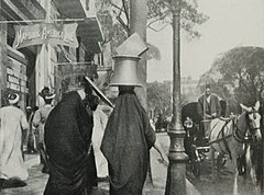 Woman Carrying a Huge Iron Cauldron on her Head in the Sharia Camel, the Principal Street of Cairo. (1911) - TIMEA.jpg