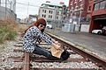 Woman in a print dress and white sunglasses sitting on a railroad track.jpg