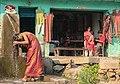 Woman washing hair outside local house in Nepal (34210641260).jpg
