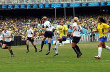 vue d'un match de football féminin, une joueuse en jaune contrôle le ballon devant deux adversaires en blanc.