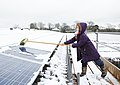Young girl cleaning photovoltaic solar panels from snow, Grange Farm, UK.jpg