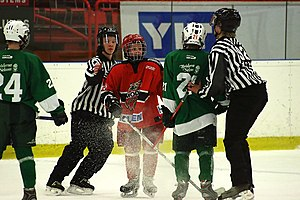 Minor ice hockey - Linesmen in the middle of breaking up a youth hockey scrum.