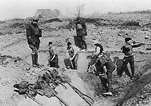 Five soldiers dig a trench, supervised by two standing above them.