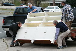 Four men lifting a heavy sideboard.