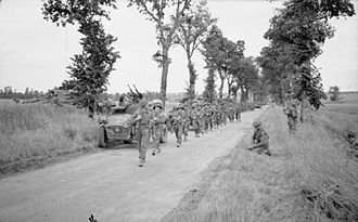 15th (Scottish) Infantry Division - Men of the 8th Battalion, Royal Scots move forward past a Humber Scout Car of 31st Tank Brigade during Operation Epsom, 28 June 1944.