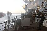 A Sailor fires a 25mm gun at sea..jpg
