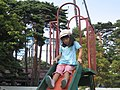 A girl playing a slide in Goryokaku Park, Misaki, Japan; August 2009.jpg