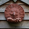 A terracotta sun ornament, Nuthurst, West Sussex, England.jpg