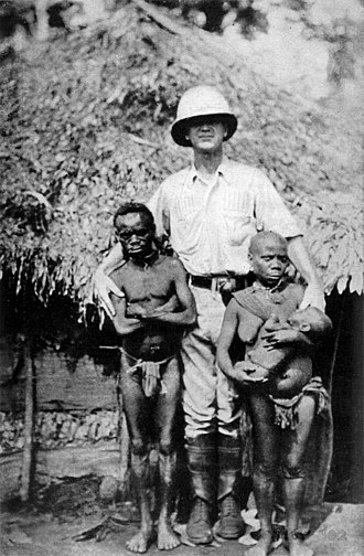 African Pygmies - Pygmy family posing with a European man for scale (Collier's New Encyclopedia, 1921)