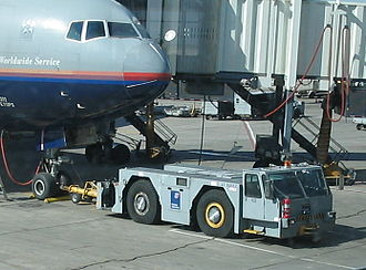 Pushback - A conventional tractor hooked up to a United Airlines Boeing 777-200ER at Denver International Airport
